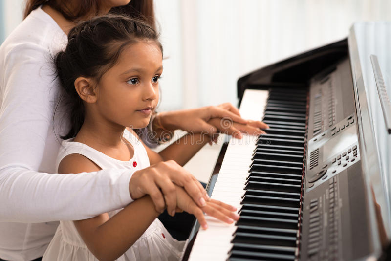 Helping to play the piano stock photos