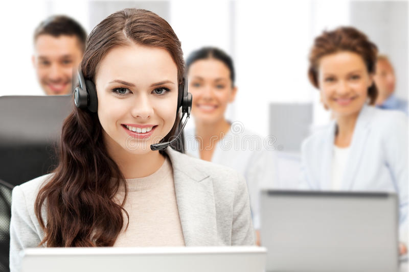 Helpline operator with headphones in call centre. Business and technology concept - helpline operator with headphones in call centre royalty free stock image
