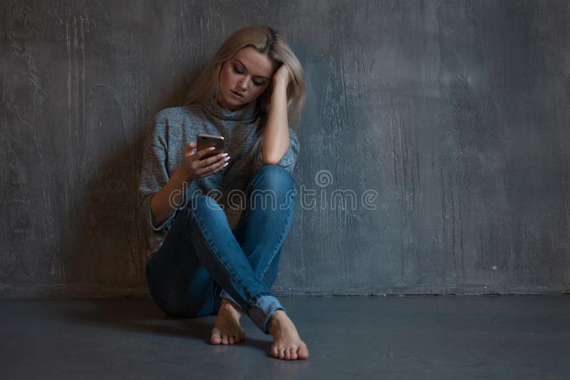 Helpline, psychological assistance. Suffering young woman sitting in a corner with a phone in her hand. royalty free stock photography