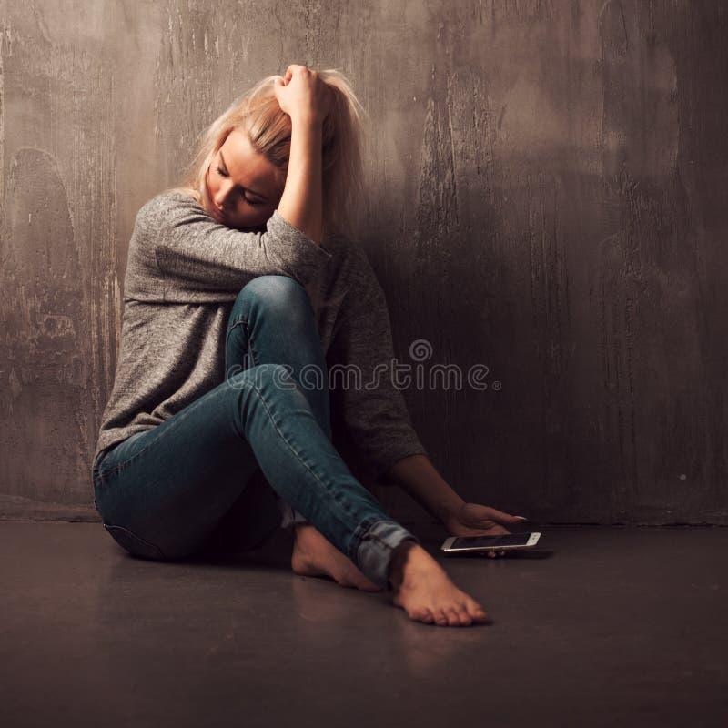 Helpline psykologisk hjälp Lida sammanträde för ung kvinna i ett hörn med en telefon i hennes hand royaltyfria bilder