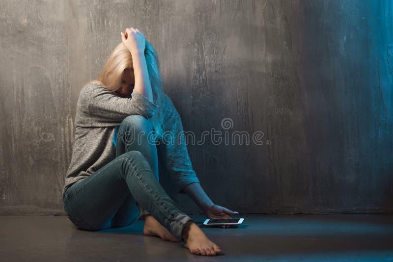Helpline psykologisk hjälp Lida sammanträde för ung kvinna i ett hörn med en telefon i hennes hand arkivfoton