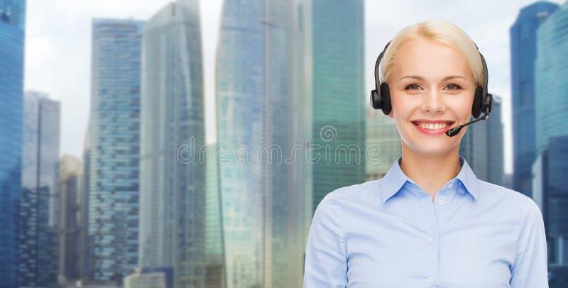 Helplineoperatör i hörlurar med mikrofon över stadsbakgrund fotografering för bildbyråer