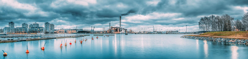 Helsínquia, Finlandia Opinião panorâmico das casas no distrito de Merihaka, zona industrial da noite do central elétrica de Hanas foto de stock