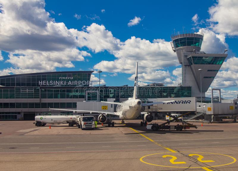 Helsinki Airport Finland 26.07.2019: Finnair airline technicians men load Luggage from container into the compartment in the tail. Of the aircraft. Two Airbus royalty free stock photo