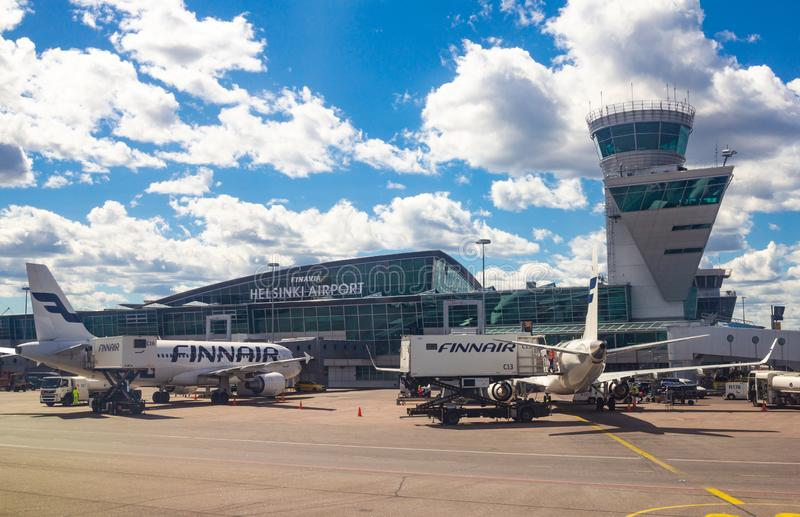 Helsinki Airport Finland 26.07.2019: Finnair airline technicians men load Luggage from container into the compartment in the tail. Of the aircraft. Two Airbus stock photography