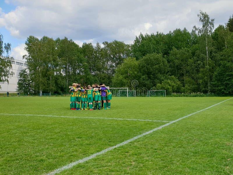 Helsinki filiżanki młodzieżowego futbolu turniej - młode chłopiec drużynowe brać strategicznego moment przed dopasowaniem zdjęcia stock