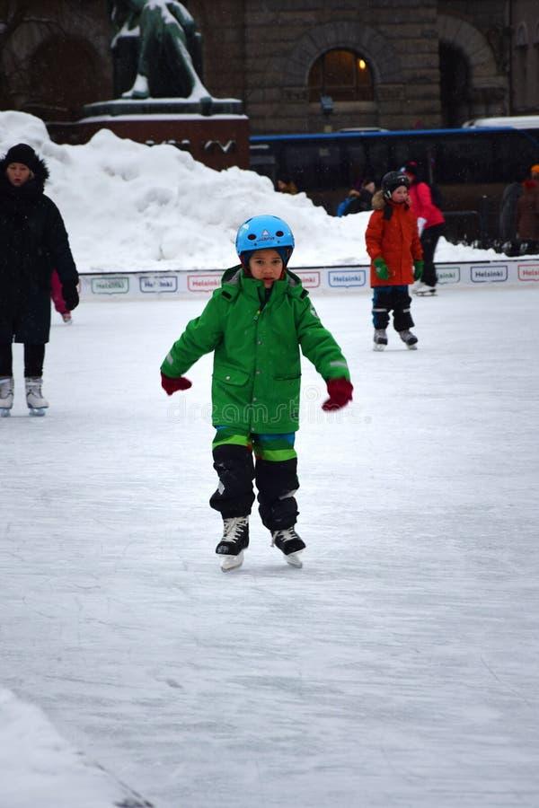 Helsinki, Finland - Januari vijftiende 2018: Een leuke jonge jongen met een groene laag die in Helsinki, Finland schaatsen royalty-vrije stock foto