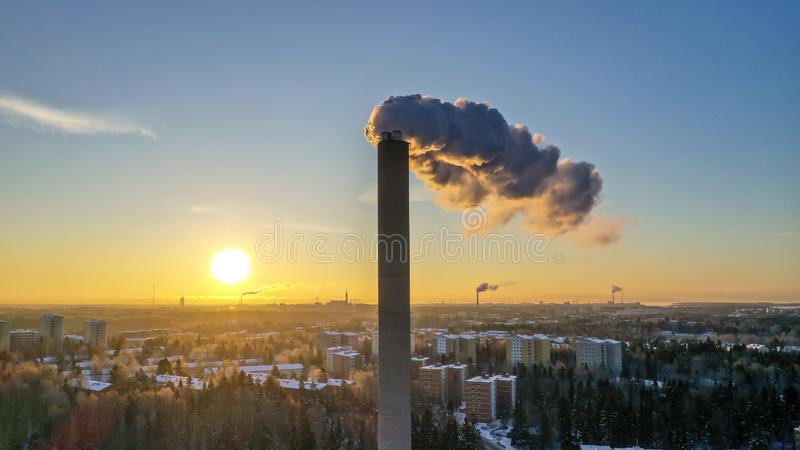 Helsinki, Finland - January 21, 2019: Smoke coming out from energy plant pipe in Helsinki on sunset time. The smoke has orange color from sunset and in the stock photography