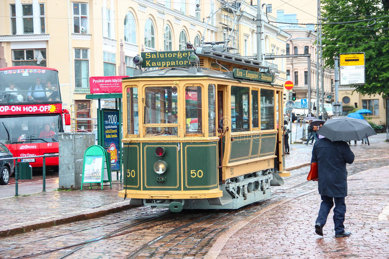 Helsinki, Finland - Jun 12 2014, Vintage sightseeing tourist tram in the city center and the pedestrian with umbrella in the rain royalty free stock image