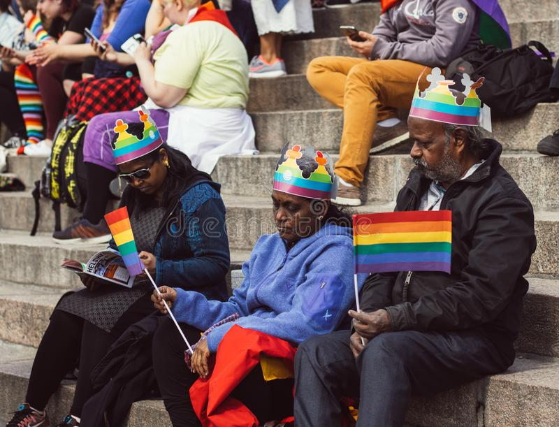 Helsinki, Finland - June 30, 2018: Indian family sitting on stairs of Cathedral on Helsinki pride festival on Senate square royalty free stock photo