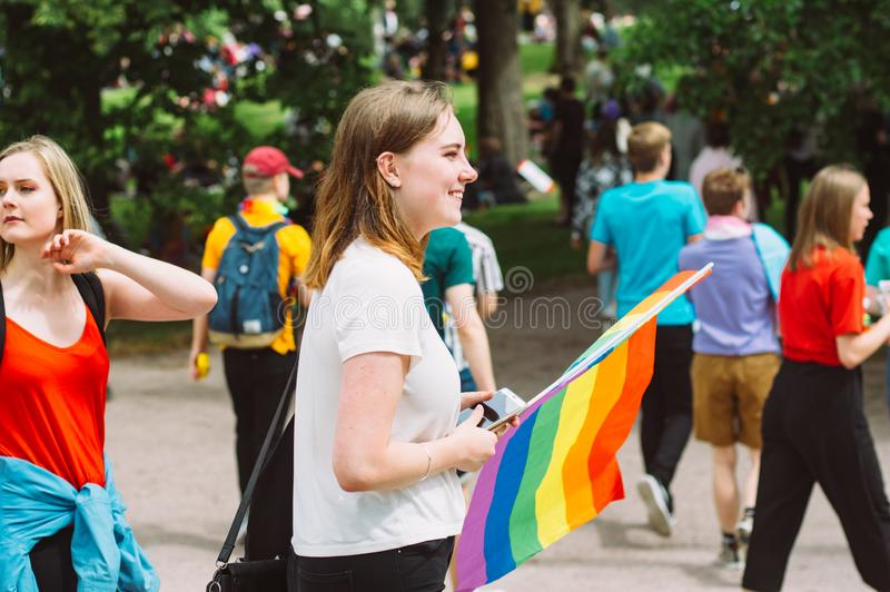 Two young girls with rainbow flag on Helsinki Pride festival in Kaivopuisto public park stock photography