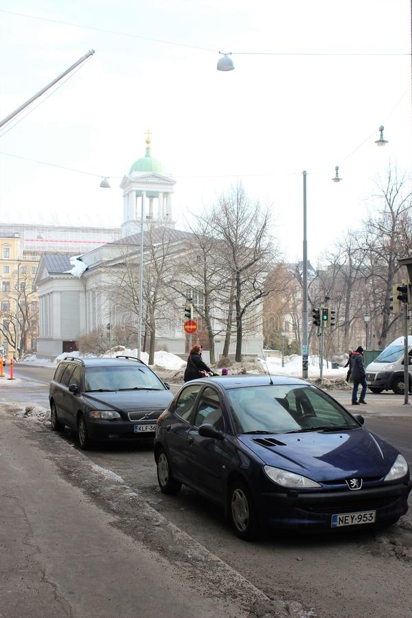 Helsinki, Finland, March 2012. City street with parked cars and old church. stock images