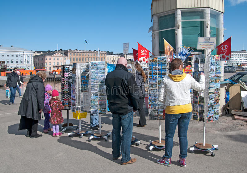 Helsinki. Finland. People buy souvenir post cards. HELSINKI, FINLAND - APRIL 16, 2011: People choose and buy sun glasses and post cards with view of Helsinki not royalty free stock photography
