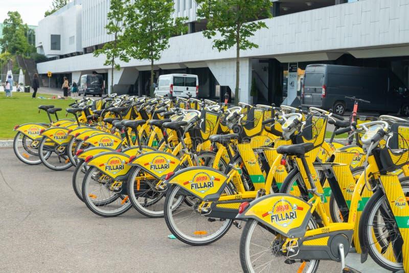 Helsinki, Finlandia - 12 de junio de 2019: Bicicletas amarillas de la ciudad para el soporte del alquiler en fila en la parte cen imagen de archivo libre de regalías