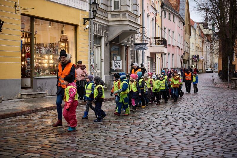 HELSINKI, FINNLAND AM 18. DEZEMBER 2018: Viele Kinder gehen in die helle hellgrüne Reflexionsweste, gehen in Stadt mit Pflegekraf lizenzfreie stockfotografie