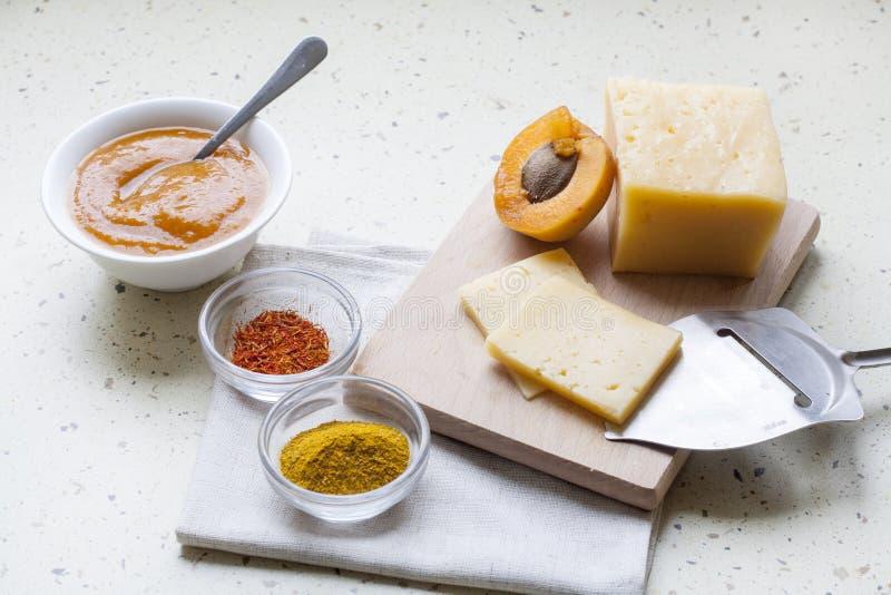 Heltäckande skivade ost med aprikoscurry i keramik, kryddor och nya aprikors royaltyfri bild