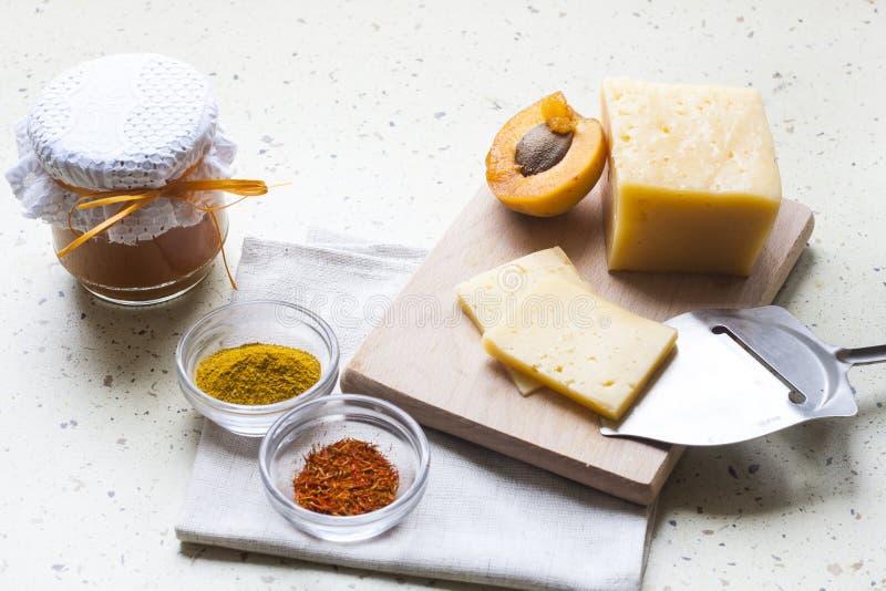 Heltäckande skivade ost med aprikoscurry i keramik, kryddor och nya aprikors royaltyfria bilder