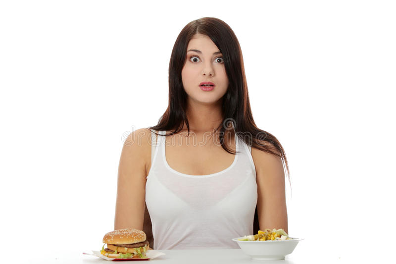 Helthy or not. Beautiful caucasian woman thinking whot to eat: hamburger or salat. Isolated on white stock photos