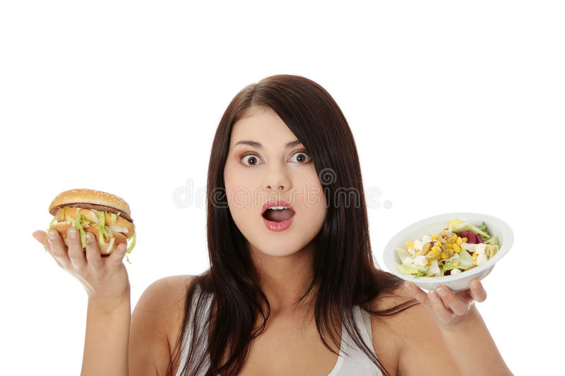 Helthy or not. Beautiful caucasian woman thinking whot to eat: hamburger or salat. Isolated on white stock images