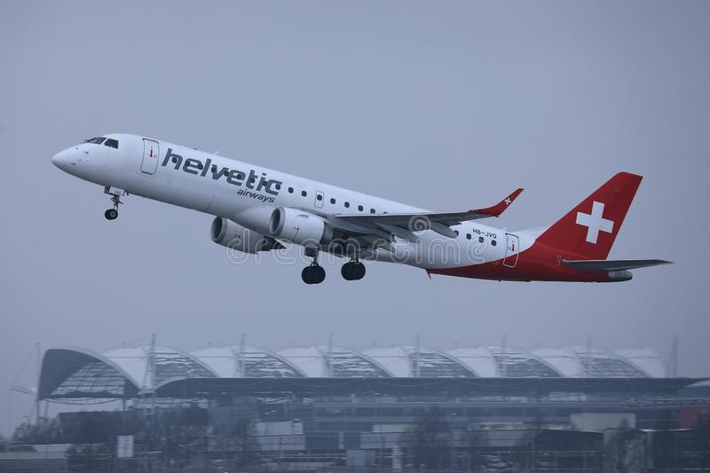 Helvetic Airways plane taking off from Munich Airport, MUC. Helvetic Airways plane approaching the airport stock image