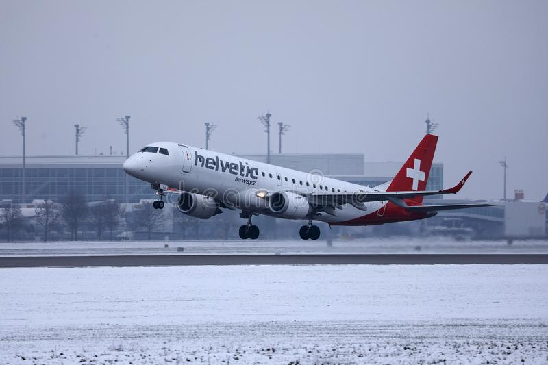 Helvetic Airways plane taking off from Munich Airport, MUC, snow. Helvetic Airways plane takes off from airport stock images