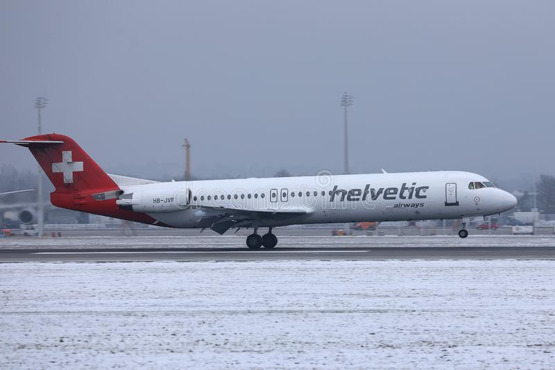 Helvetic Airways plane taking off from Munich Airport, MUC, snow. Helvetic Airways plane takes off from airport royalty free stock photos