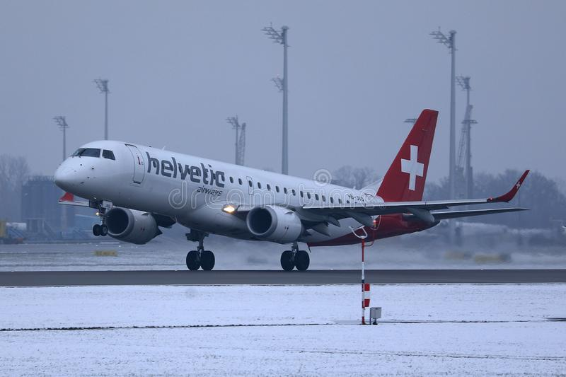 Helvetic Airways plane taking off from Munich Airport, MUC, snow. Helvetic Airways plane takes off from airport royalty free stock image