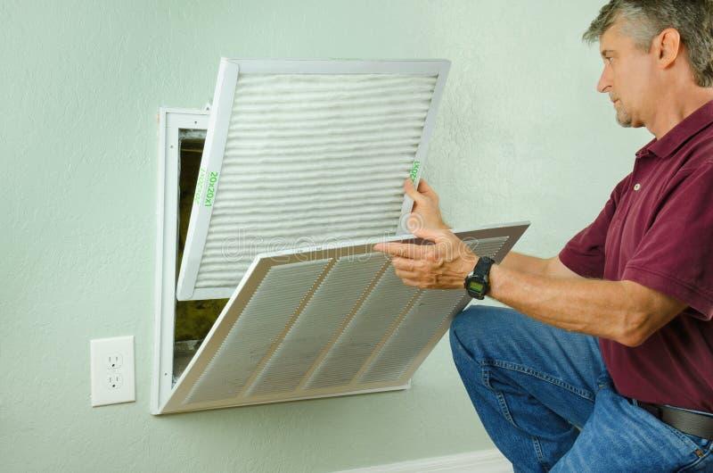 Hem- ägare som sätter det nya luftfiltret på luftkonditioneringsapparaten royaltyfri fotografi