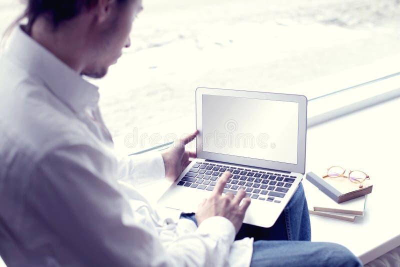Hem- användande bärbar dator för stiligt för hipster för modern man arbete för entreprenör nära fönster royaltyfria foton