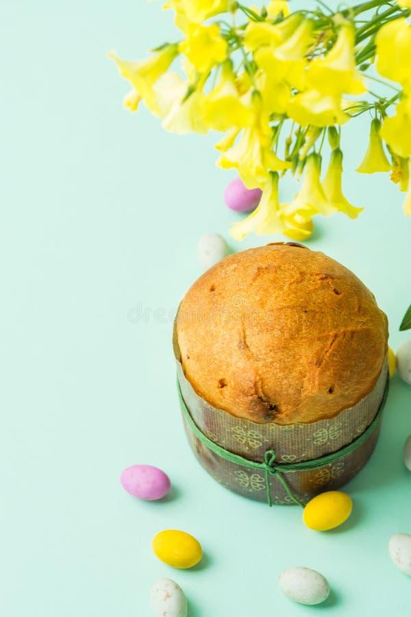 Hem- bakad söt kakaPanettone för påsk i för chokladgodis för pappers- form mångfärgade spräckliga ägg spridda på turkosbakgrund arkivfoton