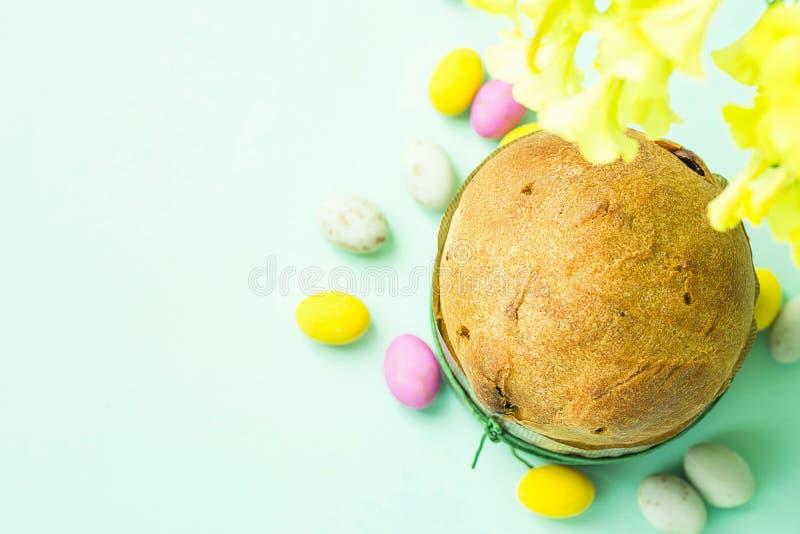 Hem bakad söt kakaPanettone för påsk i för chokladgodis för pappers- form mångfärgade spräckliga ägg spridda på turkostabletopen royaltyfria foton