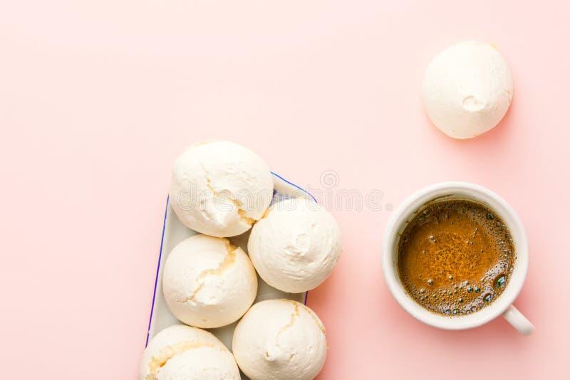 Hem- bakade marängkakor på den rektangulära koppen för efterrättplatta av nytt bryggat kaffe på ljust - rosa bakgrund arkivfoton