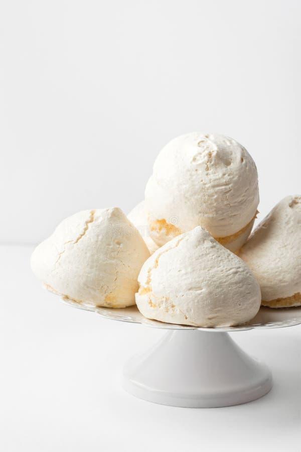 Hem- bakade marängkakor på kakaställning på vit tabellväggbakgrund Fransk italiensk schweizisk efterrättkokkonstconfection arkivfoto