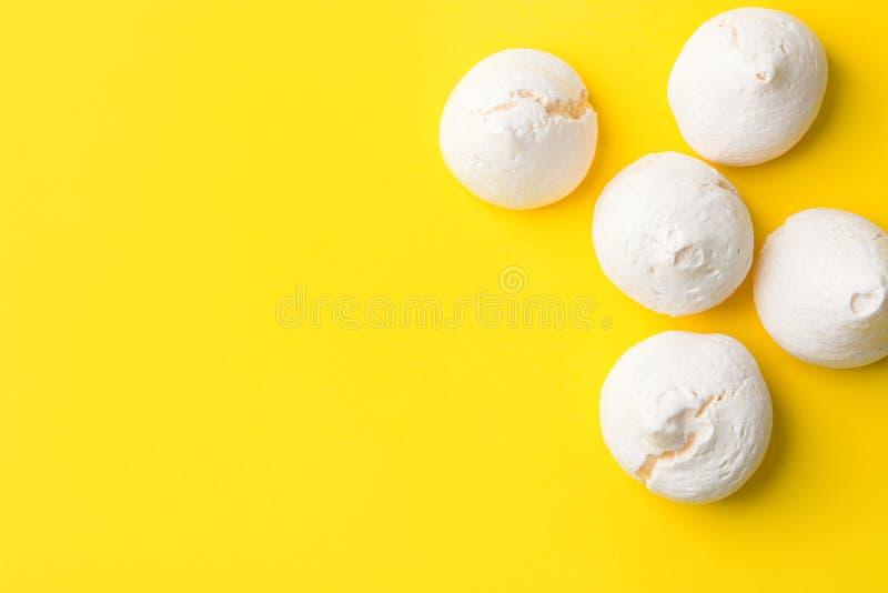 Hem- bakade marängkakor på ljus gul bakgrund Lekmanna- Minimalistl?genhet Fransk italiensk schweizisk efterrättkokkonstconfection fotografering för bildbyråer