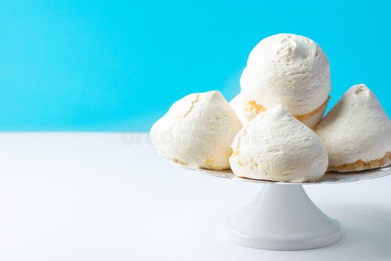 Hem- bakade marängkakor på ställning för vit kaka på blå väggbakgrund Fransk italiensk schweizisk efterrättkokkonstconfection royaltyfria foton