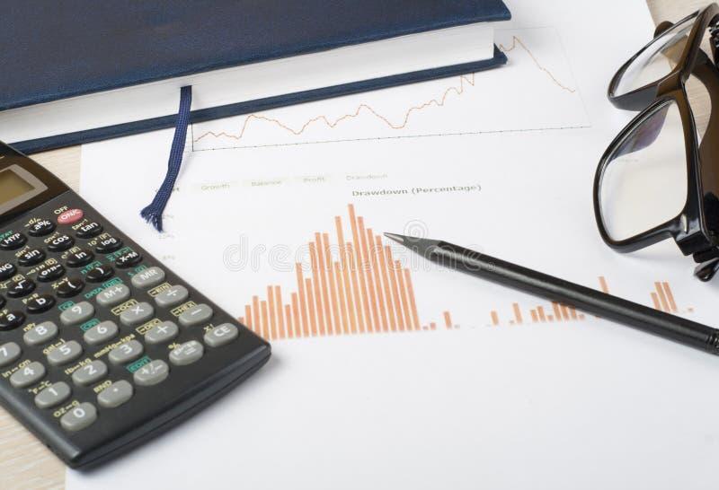 Hem- besparingar, budget- begrepp Diagram, notepad, räknemaskin och exponeringsglas på den trätabellen för kontorsskrivbord royaltyfria foton