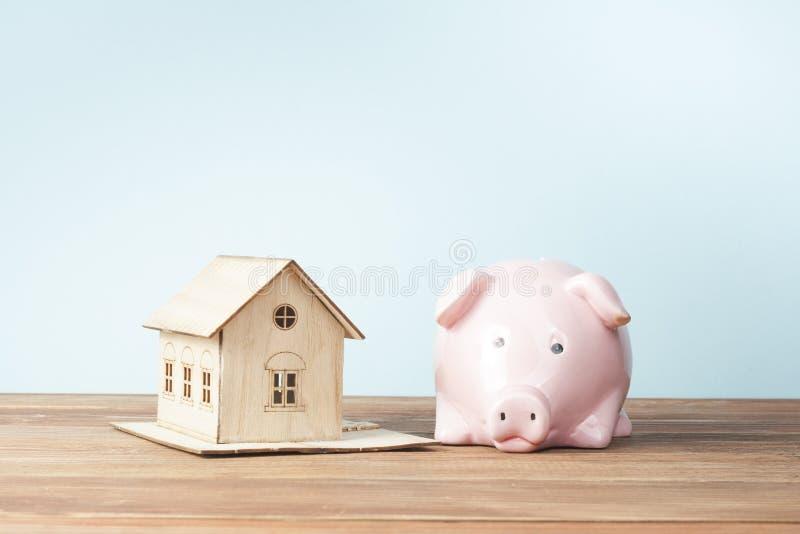 Hem- besparingar, budget- begrepp Modellera huset, notepaden, pennan, räknemaskinen och mynt på den trätabellen för kontorsskrivb royaltyfri bild