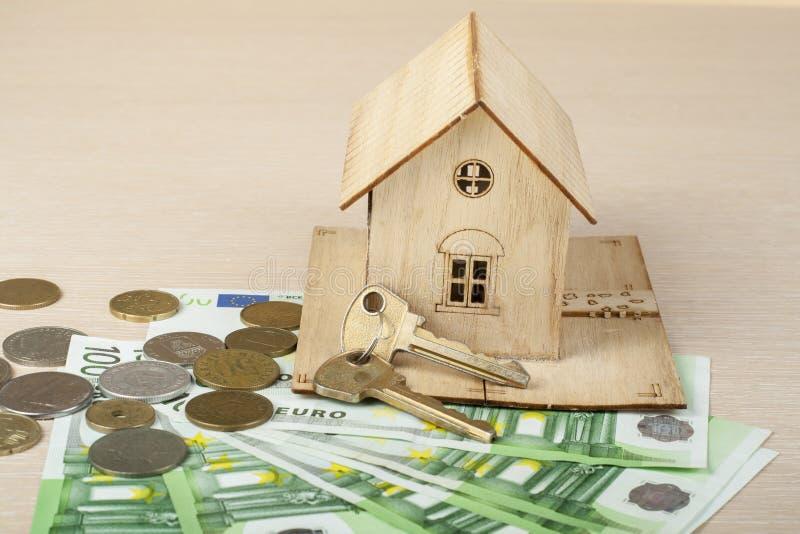 Hem- besparingar, budget- begrepp Modellhus och pengar på trätabellen royaltyfria foton