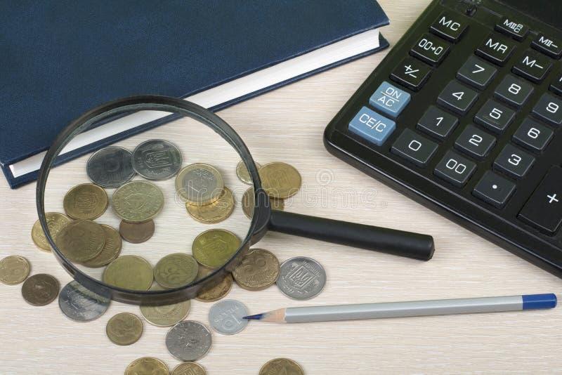 Hem- besparingar, budget- begrepp Notepad, penna, räknemaskin, förstoringsglas och mynt på träkontorstabellen royaltyfria bilder