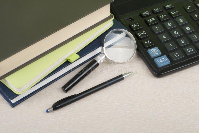 Hem- besparingar, budget- begrepp Notepad penna, räknemaskin, förstoringsglas på den trätabellen för kontorsskrivbord arkivbild