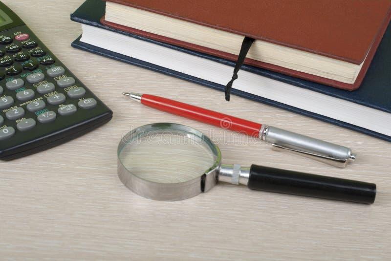 Hem- besparingar, budget- begrepp Notepad penna, räknemaskin, förstoringsglas på den trätabellen för kontorsskrivbord royaltyfria foton