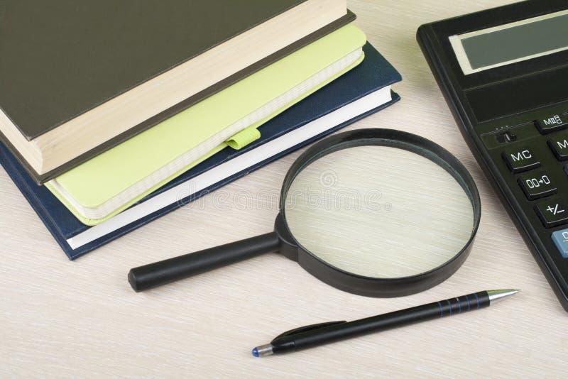 Hem- besparingar, budget- begrepp Notepad penna, räknemaskin, förstoringsglas på den trätabellen för kontorsskrivbord royaltyfri fotografi
