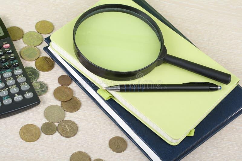 Hem- besparingar, budget- begrepp Notepad, penna, räknemaskin och mynt på den trätabellen för kontorsskrivbord royaltyfri bild