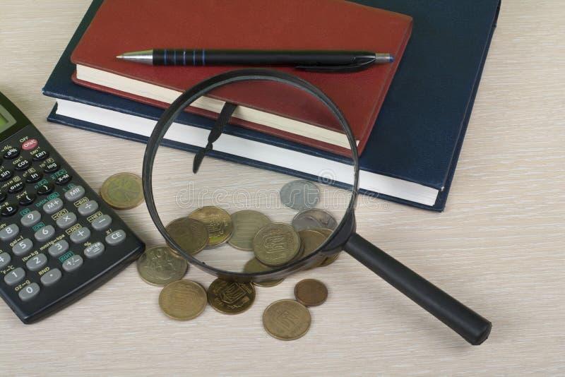 Hem- besparingar, budget- begrepp Notepad, penna, räknemaskin och mynt på den trätabellen för kontorsskrivbord fotografering för bildbyråer