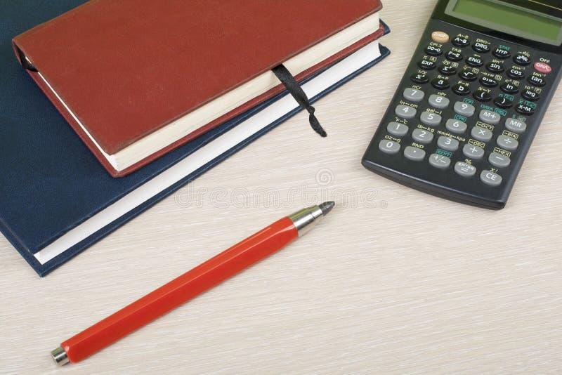 Hem- besparingar, budget- begrepp Notepad penna, räknemaskin på den trätabellen för kontorsskrivbord royaltyfria bilder