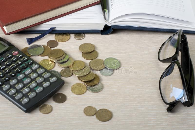 Hem- besparingar, budget- begrepp Notepad, räknemaskin, glasögon och mynt på den trätabellen för kontorsskrivbord royaltyfria foton