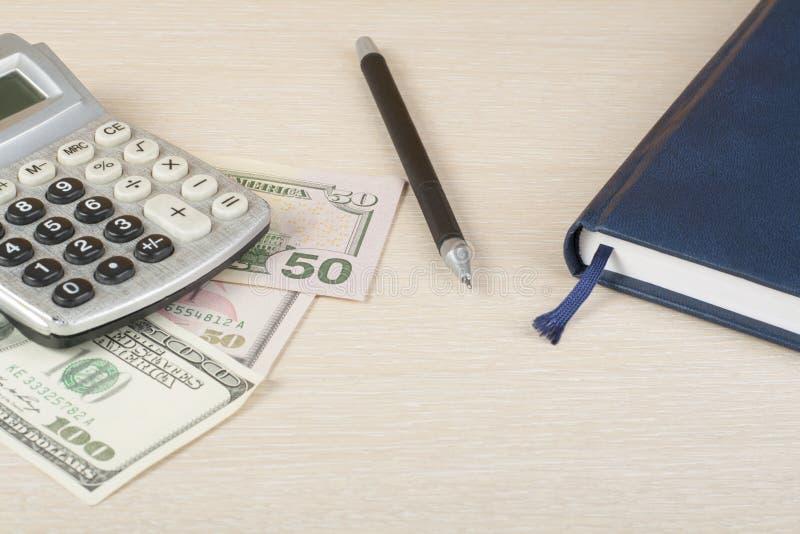 Hem- besparingar, budget- begrepp Räknemaskin, nootepad, penna och pengar på den trätabellen för kontorsskrivbord arkivbild