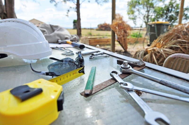 Hem- faktotumhjälpmedel på tabellen som är klar att bygga utomhus- projektuppgift arkivfoto