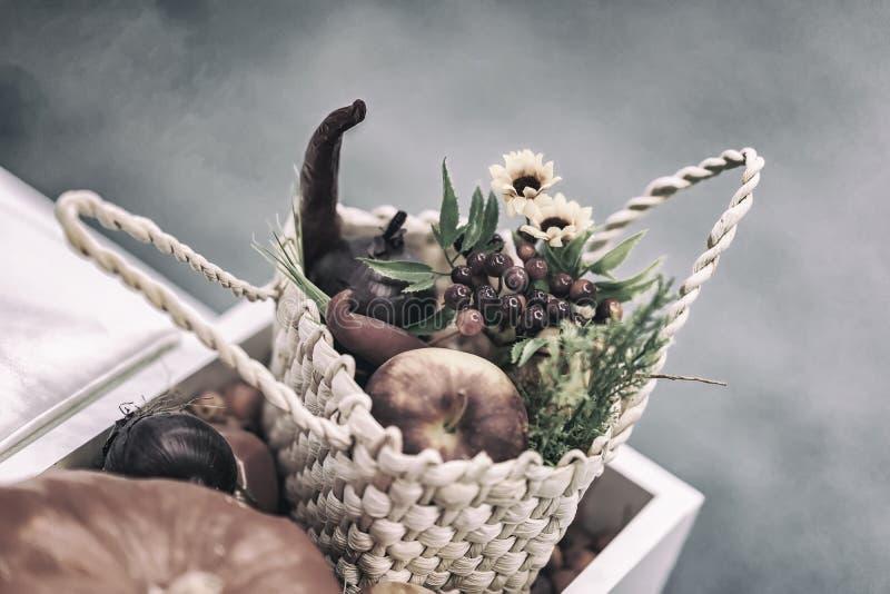 Hem- festlig blommaordning från sidor, blommor, grönsaker, frukter, bär i den lantliga vide- korgen H?st arkivbilder