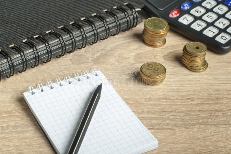 Hem- finansiell och budget- begrepp för besparingar, Räknemaskin, penna och mynt på kontorstabellen royaltyfria foton
